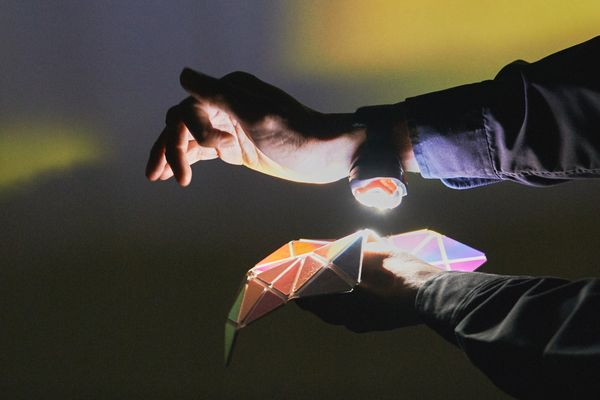 In a dark room, two arms come into shot from the right. The top arm has a small bright light strapped to the underside of the wrist, which is pointing down towards a kaleidoscopic, geometric matrix of mirror shapes held up by the other hand. Yellow and green coloured light reflects off the mirrored shapes onto the wall behind.