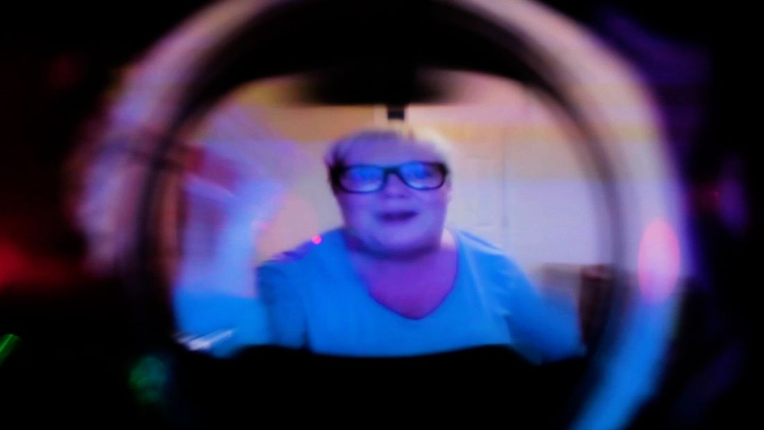 A white middle-aged woman with short blond hair and black rimmed glasses waves into a camera aperture. The image is distorted and out of focus.