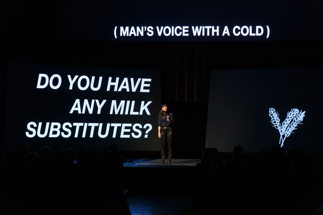 """The artist Christine Sun Kim stands on a stage in the centre of a dark room. A screen above her shows in white text """"(MAN'S VOICE WITH A COLD)"""", another to the left reads """"DO YOU HAVE ANY MILK SUBSTITUTES?"""" and to the right is a white line drawing of oats."""