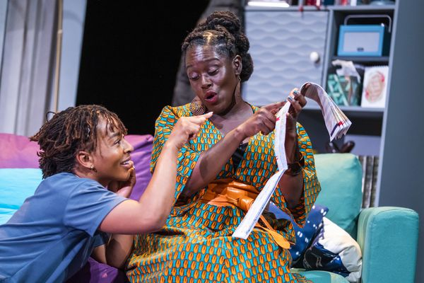 Uche Abuah and Michelle Asante on stage in Notes on Grief. Asante sits on a blue and purple sofa and holds up a folded paper map, which she points to. Abuah sits at her feet, smiling and also points at the map. Asante is Black with dark brown skin; her hair is twisted from the crown into three buns at the back of her head; she wears a bright orange and turquoise patterned dress and an orange wrap belt.  Abuah is Black with medium brown skin; her hair is in fine locks, pulled back; she wears a blue T-shirt.