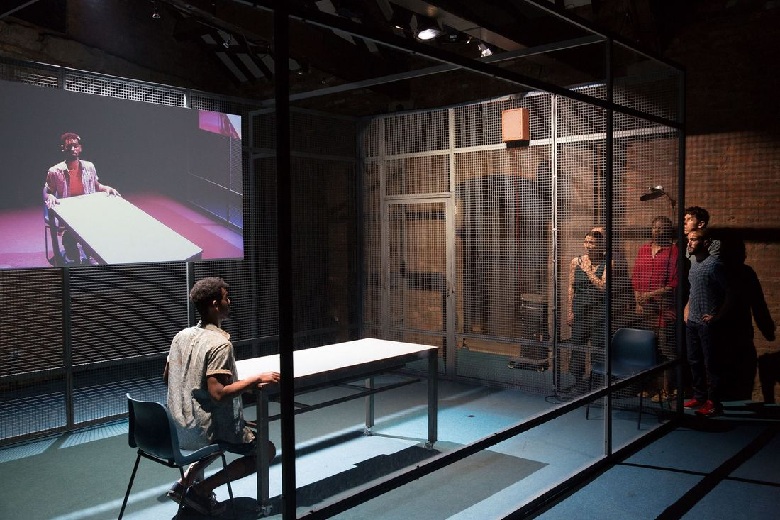 A man sits at a table in a caged room while a group of people look on from outside. An image of the man at the table is projected onto a screen behind him.