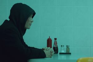 All this this unreal time thumbnail of side view of man in a hoodie sat at a table