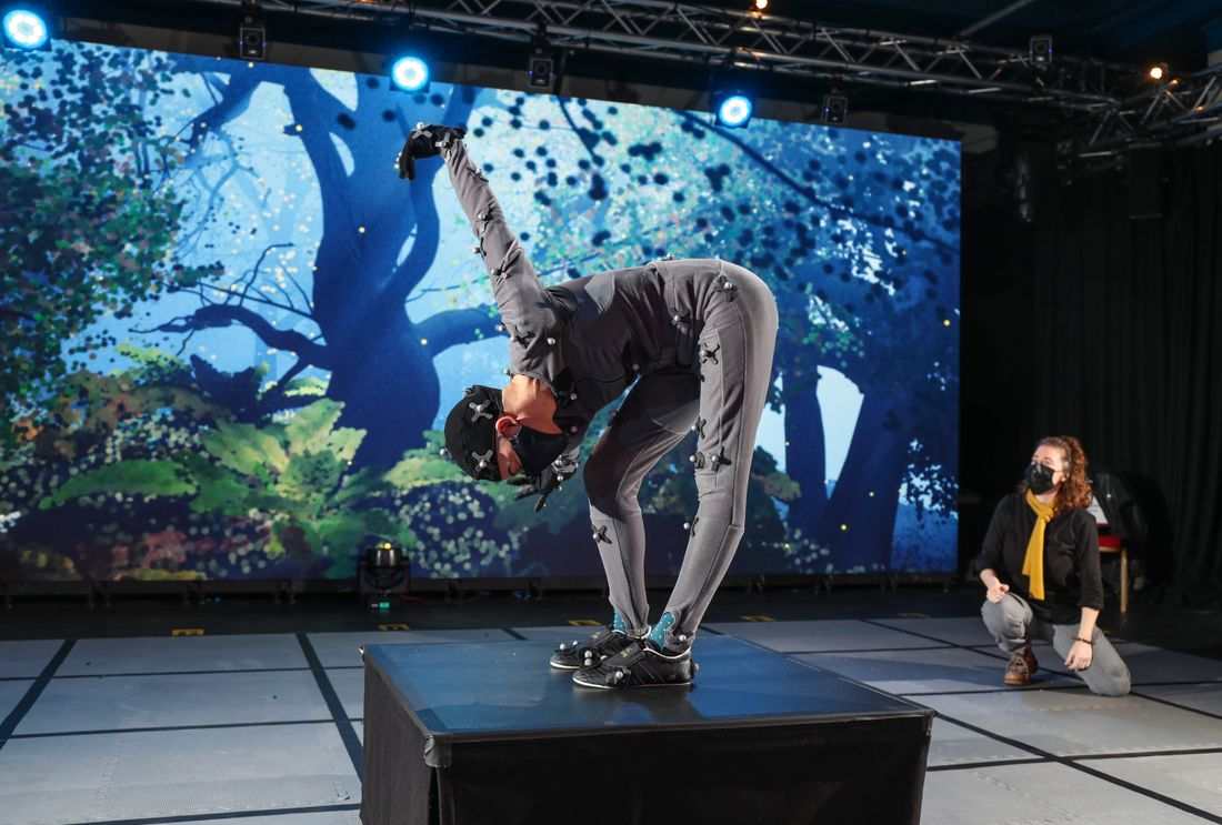A person wearing a grey motion capture suit stands bent over at the waist in front of a digital screen