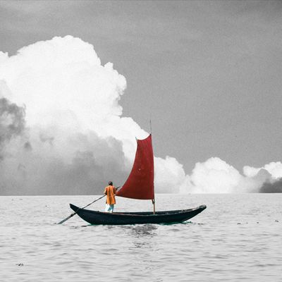 A calm sea with puffy grey and white clouds on the horizon, in black-and-white. Floating on the water's surface, in colour, is a wooden boat with a single red sail. An old man stands in the boat wearing an orange shirt and holding a large oar. In the top left-hand corner are the letters: م ل ح