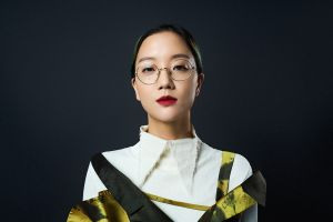 A head and shoulders portrait of the artist Christine Sun Kim. She wears her hair pulled back, round glasses and burgundy red lipstick with an off-white top with a pointy collar and a gold and black dress against a plain, dark background. She is looking directly into the lens.