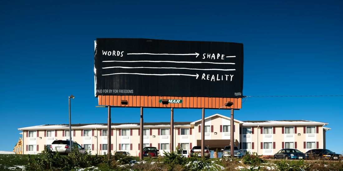 """An image of a billboard high in the blue sky over a motel. It has a black background and white text that reads """"WORDS"""" then a white arrow to the text """"SHAPE"""" then a white arrow that runs over three lines to the text """"REALITY"""""""