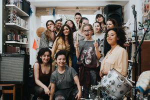 Group photo of young people inside a bedroom with audio equipment and instruments