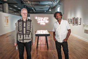 Hans Ulrich Obrist and Lemn Sissay stand in the Poet Slash Artist exhibition at HOME during MIF21. Hans Ulrich stands on the left; he is white with a pale peach skin tone and very short white hair; he wears glasses with clear frames, a green check shirt with black lattice and arrow patterns and dark navy jeans; he is smiling and looking just to the right of the camera. Lemn stands on the right; he is Black with a deep brown skin tone and medium length black and grey afro hair; he wears a white short sleeve shirt and black jeans, his hands are in the front pockets of his jeans; he smiles with a closed mouth directly at the camera. A vitrine can be seen between them in the background, and beyond that a neon artwork on the wall; a large frame hangs on the left wall behind Hans Ulrich; many smaller frames hang on the right wall behind Lemn. The industrial style ceiling of the space can be seen above the white gallery walls and partitions.