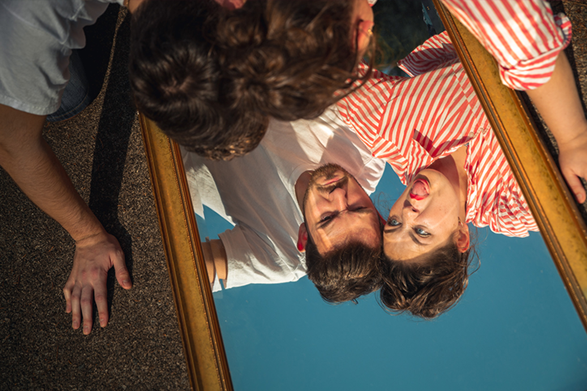 two people who looking into a mirrow upside down pulling fiunny faces