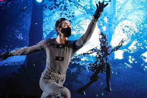 Man in grey costume performing in front of a screen projection