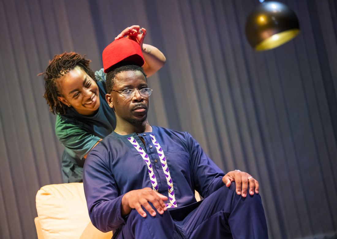 Uche Abuah and Itoya Osagiede on stage in Notes on Grief. Osagiede is Black with dark brown skin, short black hair, moustache and goatee beard; he sits on a yellow armchair wearing a blue dashiki with white and purple details over blue trousers, he wears glasses and has a serious expression. Abuah stands behind him and laughs as she holds a red hat above his head. Abuah is Black with medium brown skin; her hair is in fine locks, pulled back; she wears a blue T-shirt and trousers.