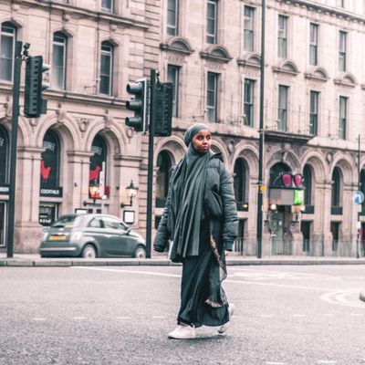 Ebyan is walking down Portland Street in Manchester city centre. She is looking at something in the distance.