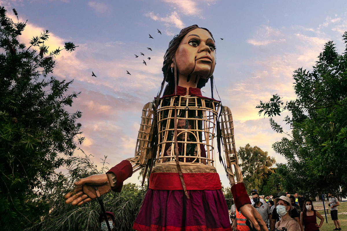 The Little Amal puppet, with one of the puppeteers nestled inside, looks around her in a Turkish park. Behind her head are a flock of birds in the late evening sky, and a procession of people follow after her.