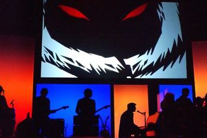 Silhouette of a band in front of a large screen projection