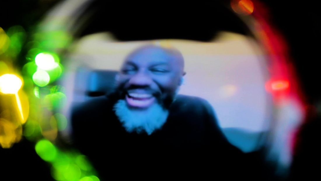 A blurred and light-distorted image down a dark camera lens of a laughing person who has black skin, a bald head and a bushy black and white beard.