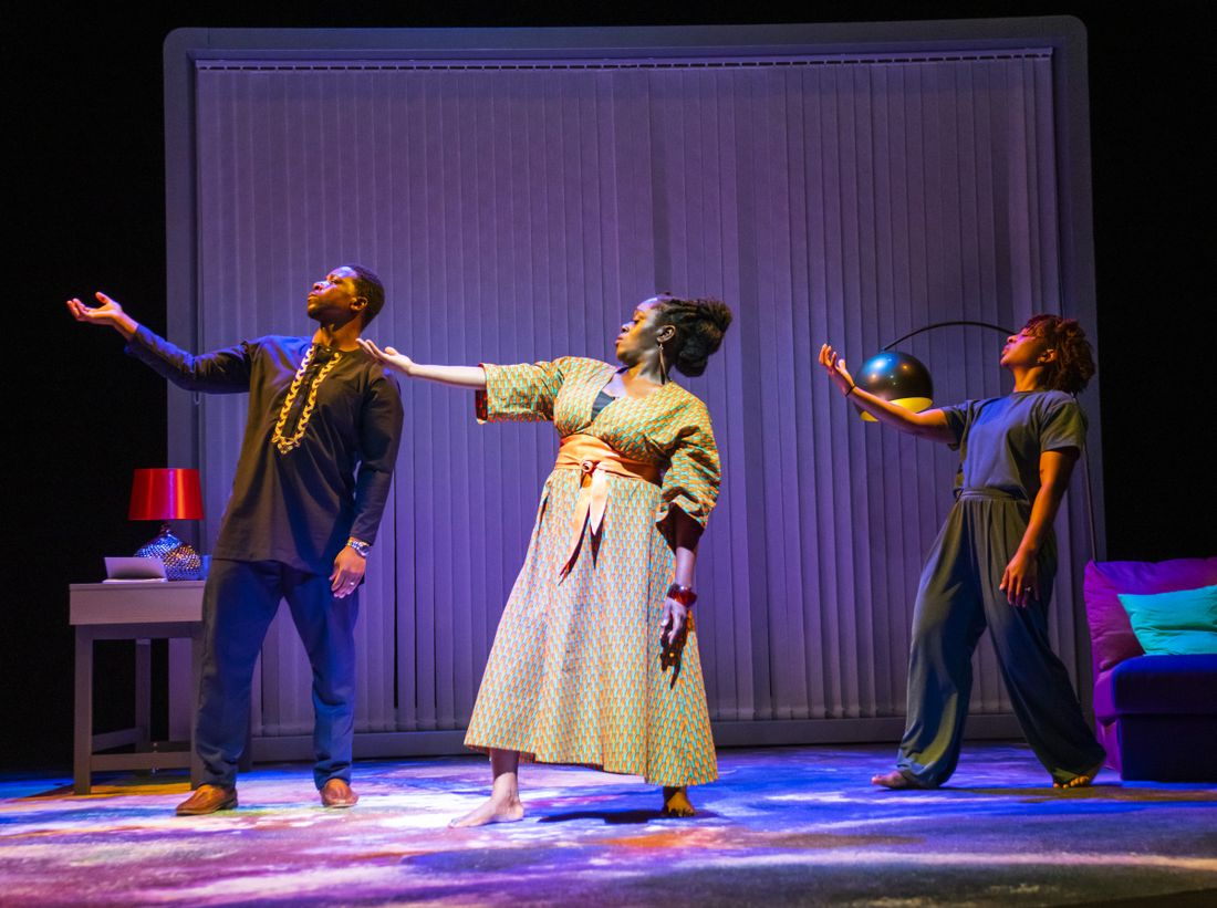 Itoya Osagiede, Michelle Asante and Uche Abuah on stage in Notes on Grief. All three stand on the stage in a line striking the same pose, facing forward, twisting to the right with their right arm raised to shoulder height and their face turned towards their raised hand.