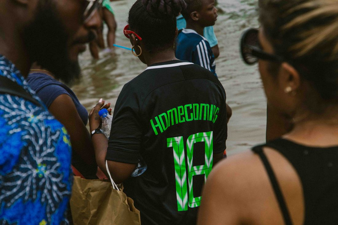 An image of people standing in the sea in Lagos, Nigeria, during Homecoming festival 2018. Most people are seen from the back or side; two people in the foreground frame the image, and in the centre a person wears a football shirt with 'Homecoming 18' printed on the back, red sunglasses and gold hoop earrings.
