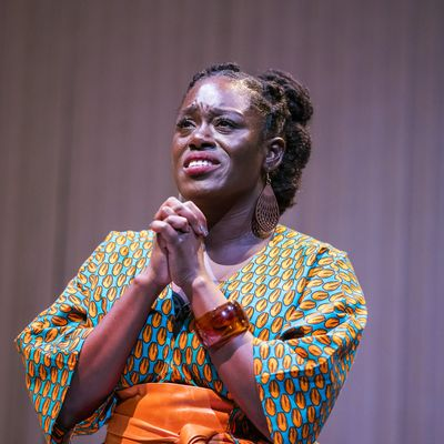 Michelle Asante on stage in Notes on Grief. Asante stands with her hands pressed together with fingers intertwined, her brow is furrowed as if in pain, her eyes look upward as if in prayer. Asante is Black with dark brown skin; her hair is twisted from the crown into three buns at the back of her head; she wears a bright orange and turquoise patterned dress and an orange wrap belt.