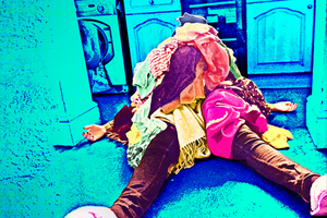 Woman lying on the floor of a kitchen with a pile oflaundry on top of her