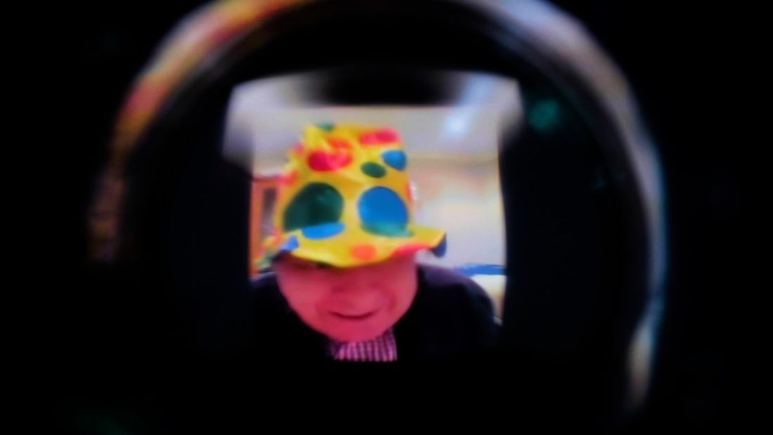 A blurred and light-distorted image down a dark camera lens of an older person with white skin wearing a bright polka-dot clown hat.