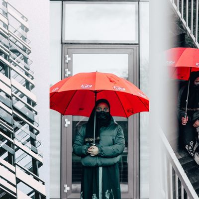 A set of three images together. On the left is a tall building with glass and metal panels of irregular length arranged horizontally, with gaps in between the panels. In the middle, Ebyan is now wearing glasses, a mask and holds a red umbrella in front of a door. On the right, she is holding the umbrella while sat on concrete steps with grey railings either side.