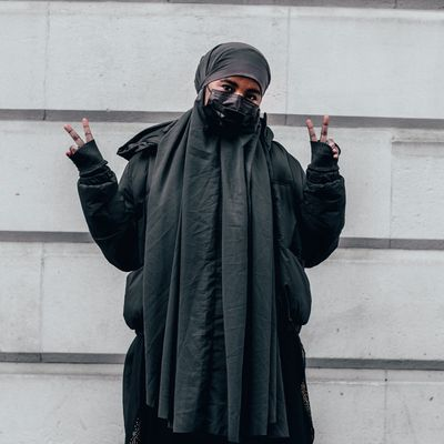 A young woman is wearing a grey hijab, puffer jacket and mask makes a peace sign with both her hands. She is stood in front of white stone bricks. (The young woman, Ebyan, appears in all of Saidul's photographs here.)